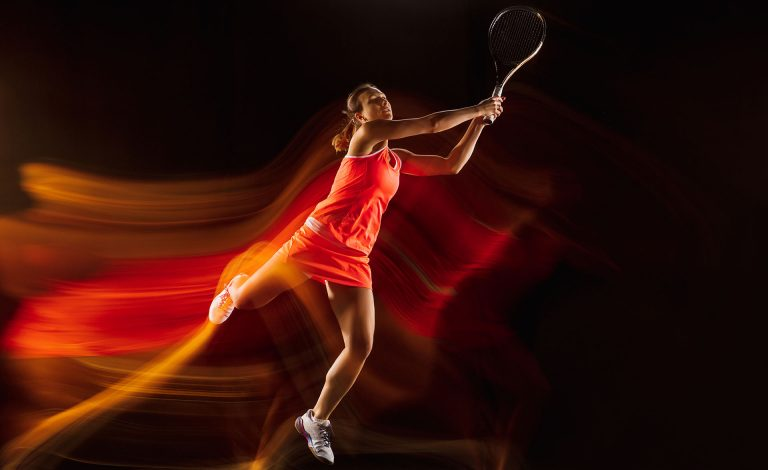 professional-female-tennis-player-training-isolated-black-studio-background-mixed-light-woman-sportsuit-practicing